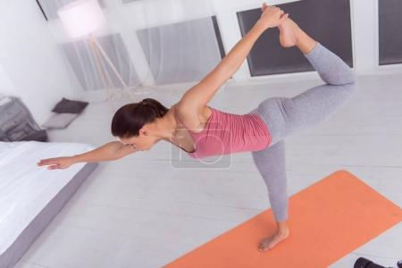 Happy woman exercising on the carpet at home