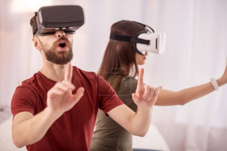 Startled surprised man has fun with VR glasses