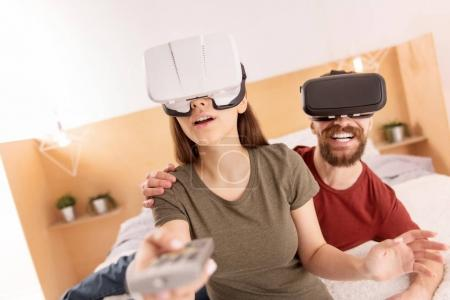 Cute startled couple adjusting VR glasses