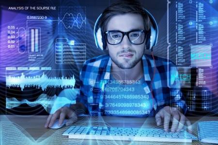 Photo pour Compliqué. Sérieux attentionné jeune programmeur étant concentré en assis devant un écran transparent modern ou essayant de trouver une erreur dans son programme sur les renseignements personnels - image libre de droit