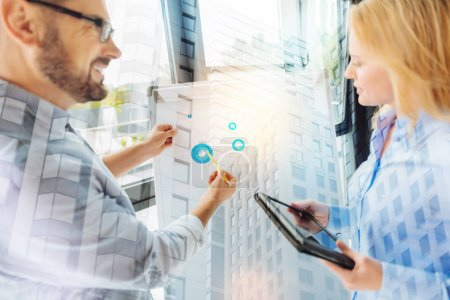 Cheerful man showing diagrams to his attentive coworker