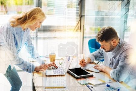 Young man making notes while his colleague working on the laptop