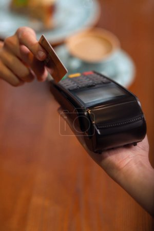 Human hand holding plastic card in payment machine