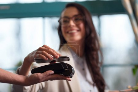 Cheerful merry woman paying with nfc technology