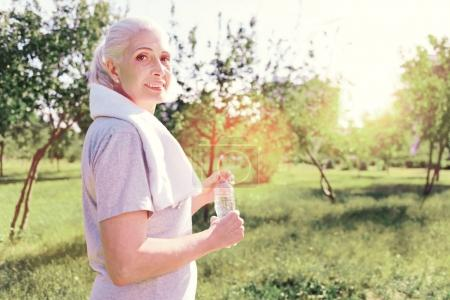 Portrait of optimistic elderly woman with a bottle of water