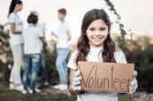 Happy cute girl being a volunteer