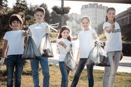 Nice cheerful children holding litter bags