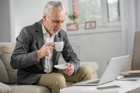 Foto de Mantener su atención. Atractivo empresario sosteniendo la copa en la mano derecha y manteniendo la sonrisa en su rostro mirando en el ordenador - Imagen libre de derechos