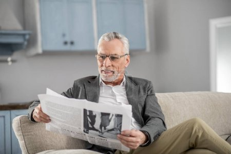 Happy mature man looking at newspaper