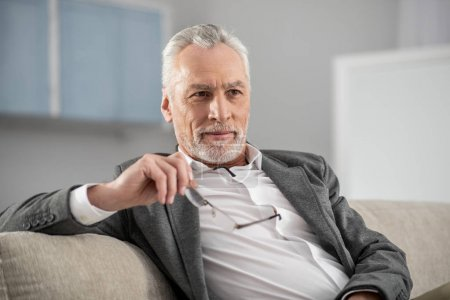 Attractive bearded male person dreaming about vacation