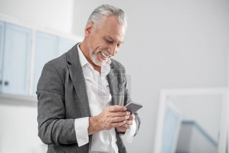 Delighted man reading pleasant message
