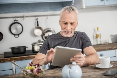 Attentive bearded male person typing message