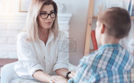 Photo pour Crois-moi. Dame joyeuse souriant tout en regardant un adolescent et en essayant d'établir un contact et une confiance avec un jeune patient . - image libre de droit