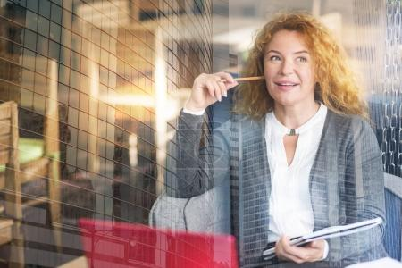 Charming businesswoman being deep in thoughts
