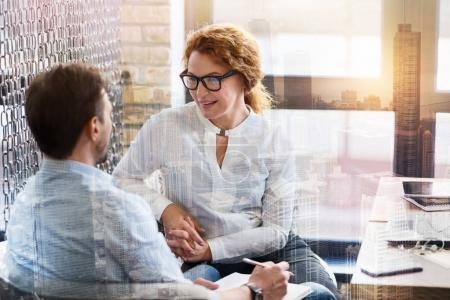 Photo pour Conversation agréable. Femme jolie rousse à lunettes, assis à côté de son collègue masculin et en bavardant avec lui pendant la pause au travail - image libre de droit