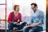 Cheerful couple chatting while working on window sill