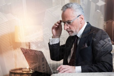 Serious mature businessman working on laptop
