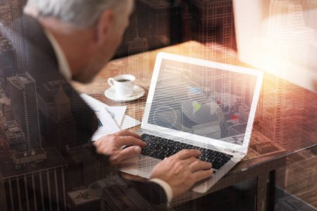 Photo for Innovative strategies development. Selective focus on a laptop used by a successful man wearing suit sitting at a table and working on a new business plan. - Royalty Free Image