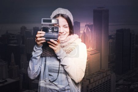 Cheerful smiling woman in a warm hat taking photos