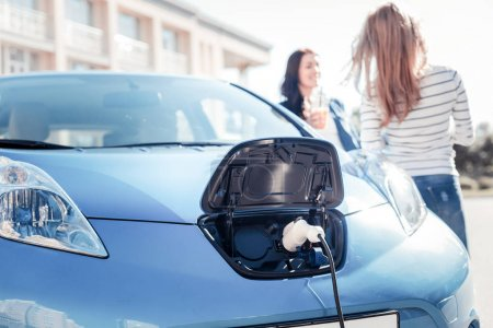 Blue comfortable car staying and charging.