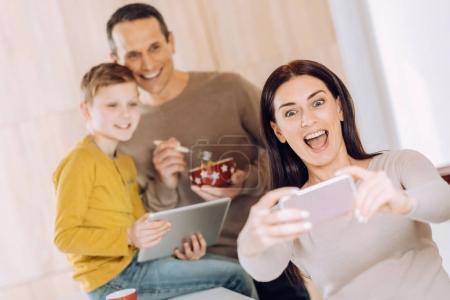 Joyful woman taking selfie of her family