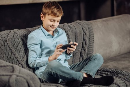 Pleasant boy sitting on sofa and playing on phone