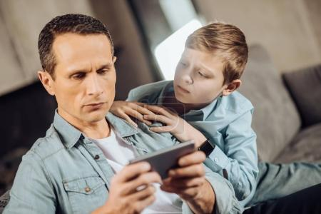 Upset boy searching attention from his father