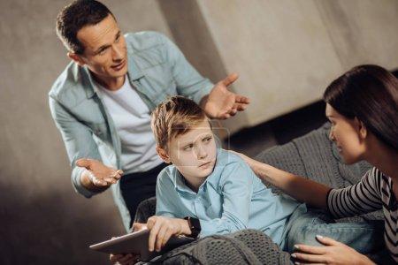 Pre-teen boy glaring at parents interrupting his game