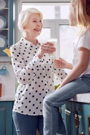 Pleasant woman offering her granddaughter to drink milk