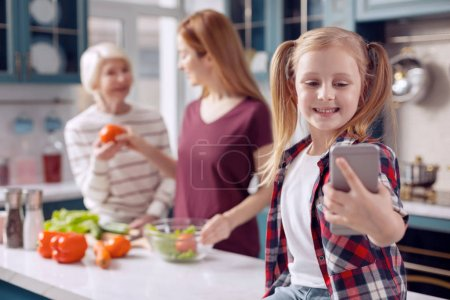 Smiling girl taking selfie while mother and grandmother cooking
