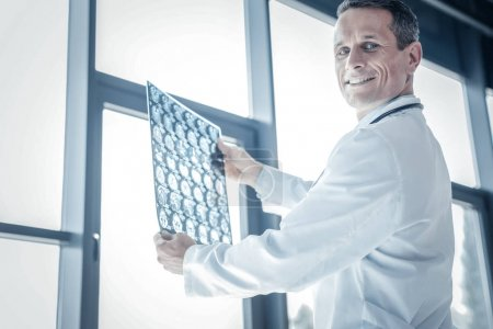 Photo for I know what to do. Confident skilled handsome medic being in the cabinet near the window smiling and holding x-ray scan. - Royalty Free Image