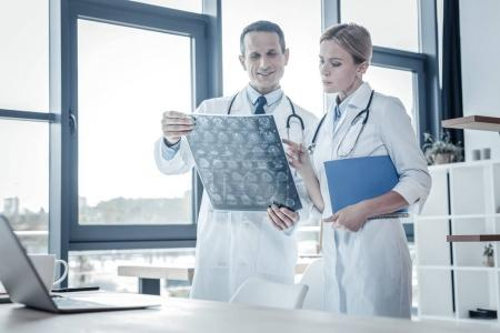 Photo for Check it out. Qualified confident perspective medics working together standing in the cabinet and examining x-ray scan. - Royalty Free Image