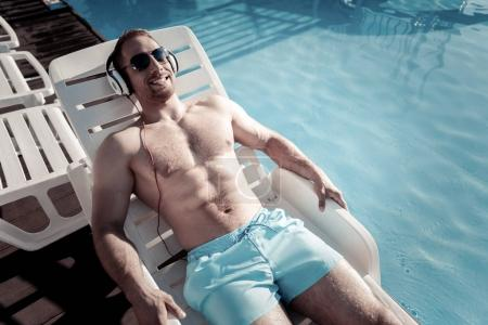Beaming young man sunbathing and listening to music
