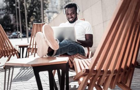 Joyful african american gentleman listening to music while using laptop
