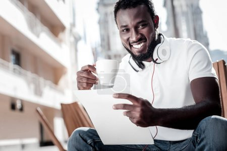 Beaming young man reading business document and drinking coffee