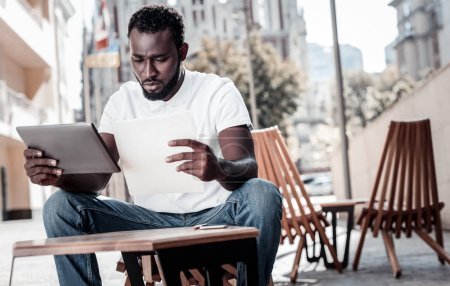 Serious male entrepreneur thinking over business documents outdoors