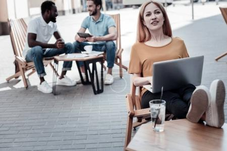 Pensive lady dreaming while using her laptop outdoors