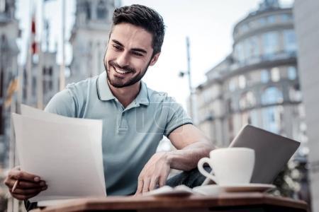 Fröhlicher Geschäftsmann arbeitet im Café mit Dokumenten