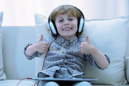 Photo for Great game. Positive cute smiling boy looking delighted while sitting with a tablet on his knees - Royalty Free Image