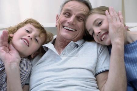 Happy old man communicating with grandchildren