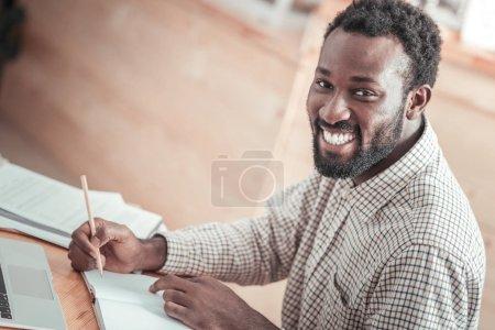 Joyful nice man doing his home task