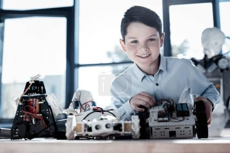 Curious little boy smiling into camera after working on robot
