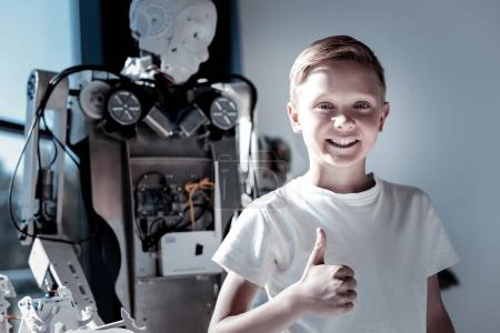 Satisfied kid standing next to robot and thumbing up