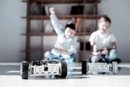 Photo for Real men activity. Selective focus on robotic toys driven by extremely excited friends sitting on the floor and battling while playing during their leisure time. - Royalty Free Image