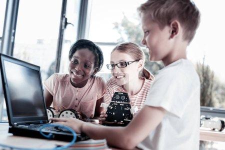 Smiling children designing program for their robotic machines