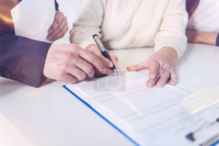 Put it here. Close up of insurance contract while an elderly woman signing it and meeting with insurance agent