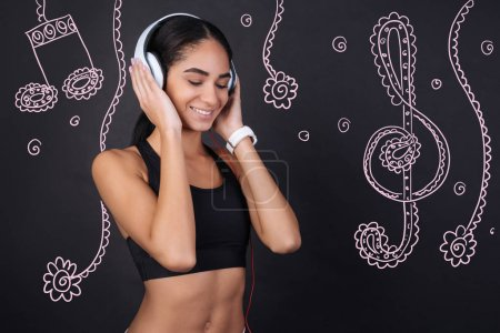 Lovely music. Cheerful young slim woman feeling good and closing her eyes while listening to pleasant music in big convenient headphones