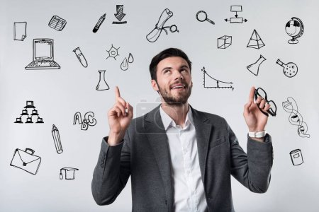 Photo for Interesting ideas. Smart creative young teacher holding his glasses and looking up while thinking about an unusual idea connected with his research work - Royalty Free Image