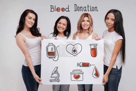 Blood donation. Cheerful responsible young women looking confident and friendly while encouraging people to donating blood