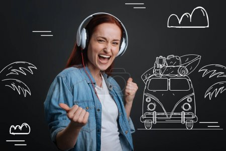 Energetic woman listening to music in headphones and dreaming about traveling